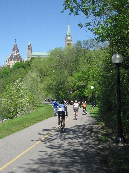 cyclists behind behind Parliament Buildings