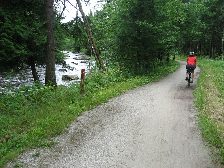 cyclists on trail next to small river