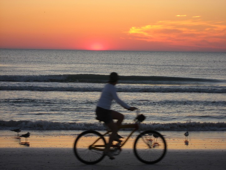 bicycling on beach with sunset